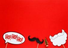 Puntelli variopinti della cabina della foto per la festa di Natale - barba, il Babbo Natale, baffi su fondo rosso Natale e decora immagine stock