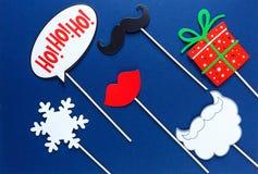 Puntelli variopinti per la festa di Natale - labbra rosse, fiocco di neve, regalo, baffi della cabina della foto su fondo blu fotografia stock