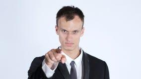 Punti dell'uomo d'affari alla macchina fotografica, fondo bianco Immagini Stock