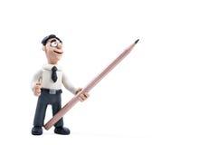 Punti dell'uomo d'affari della plastilina con una matita lateralmente Fotografia Stock Libera da Diritti