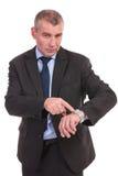 Punti dell'uomo di affari al suo orologio Fotografia Stock Libera da Diritti