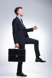 Punti dell'uomo di affari con la cartella Immagini Stock Libere da Diritti