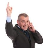Punti dell'uomo di affari su mentre sul telefono Immagini Stock