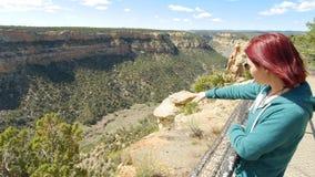 Punti della donna a qualcosa attraverso il canyon del deserto immagine stock