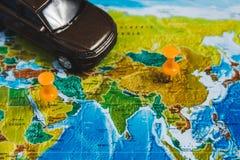Punti di destinazione automobilistici di viaggio sulla mappa di mondo indicata con le puntine da disegno variopinte e la profondi Fotografia Stock