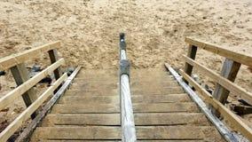 Punti di legno alla spiaggia giallo sabbia fotografie stock