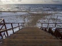 Punti di legno - giù alla spiaggia sabbiosa nel Mar Baltico un giorno nuvoloso di inverno al tramonto in Klaipeda, Lituania fotografia stock libera da diritti