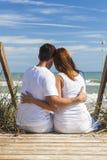 Punti di seduta romantici della spiaggia delle coppie della donna & dell'uomo Fotografia Stock Libera da Diritti