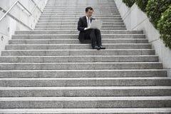 Punti di Using Laptop On dell'uomo d'affari Immagini Stock Libere da Diritti