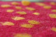Punti gialli su una feltratura rossa del fondo, lana Immagini Stock Libere da Diritti