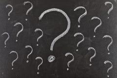 Punti interrogativi sulla lavagna Immagine Stock