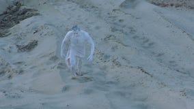 Punti sconosciuti dell'uomo sulla sabbia stock footage