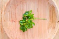 Puntilla del perejil verde fresco en una placa de madera fotos de archivo