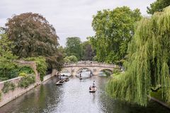 Punting on the Cam River in Cambridge, England. Very popular in Cambridge entertainment - Punting - riding on flat boats with the help of a pole, which you need Royalty Free Stock Image