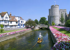 Punting in Canterbury. A punt on the moat of Canterbury castle with flower beds and the Northern gatehouse in the background. Canterbury, England stock photography