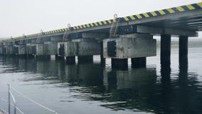 Puntmening van varend schip voorbij dam in overzeese baai Schip die naast scheepswerf varen stock videobeelden
