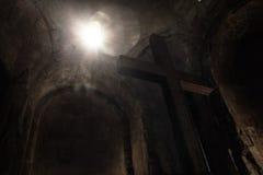 Punto abstracto del sol que brilla a través de la ventana en la cruz de piedra Imágenes de archivo libres de regalías