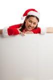 Punto asiático de la muchacha de Santa Claus de la Navidad abajo para esconder la muestra Imagenes de archivo