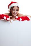 Punto asiático de la muchacha de Santa Claus de la Navidad abajo para esconder la muestra Imagen de archivo