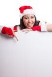 Punto asiático de la muchacha de Santa Claus de la Navidad abajo para esconder la muestra Foto de archivo libre de regalías