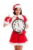 Punto asiático de la muchacha de Santa Claus de la Navidad al reloj en la medianoche Imágenes de archivo libres de regalías