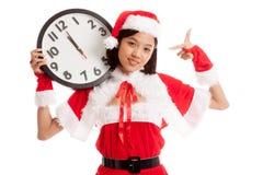 Punto asiático de la muchacha de Santa Claus de la Navidad al reloj en la medianoche Imagen de archivo libre de regalías