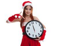 Punto asiático de la muchacha de Santa Claus de la Navidad al reloj en la medianoche Foto de archivo libre de regalías