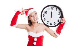 Punto asiático de la muchacha de Santa Claus de la Navidad al reloj en la medianoche Fotografía de archivo