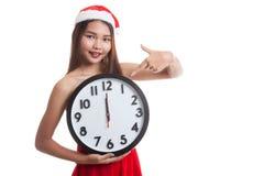 Punto asiático de la muchacha de Santa Claus de la Navidad al reloj en la medianoche Fotos de archivo