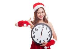Punto asiático de la muchacha de Santa Claus de la Navidad al reloj en la medianoche Imagen de archivo