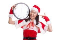 Punto asiático de la muchacha de Santa Claus de la Navidad al reloj en la medianoche Foto de archivo