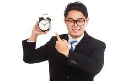 Punto asiático de la sonrisa del hombre de negocios al despertador Fotografía de archivo