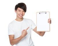 Punto asiático del finger del hombre joven a la página en blanco del tablero Imágenes de archivo libres de regalías