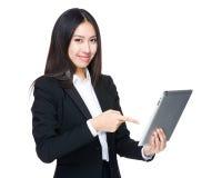 Punto asiatico del dito della donna di affari alla compressa immagine stock