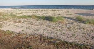Punto bajo que tira sobre la bahía y la playa arenosa y el mar almacen de metraje de vídeo