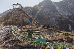 Punto de la montaña del montar a caballo de los yacs con las banderas tibetanas del rezo con luz del sol y el cielo claro en invi Foto de archivo libre de regalías
