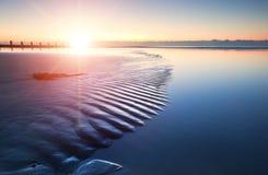 Salida del sol vibrante de la playa hermosa de la marea baja Foto de archivo libre de regalías