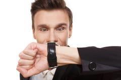 Punto del hombre de negocios en su reloj aislado, el tiempo es oro fotografía de archivo