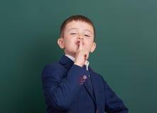 Punto del ragazzo di scuola il dito vicino al fondo in bianco della lavagna, vestito in vestito nero classico, allievo del gruppo Immagine Stock