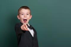 Punto del ragazzo di scuola il dito vicino al fondo in bianco della lavagna, vestito in vestito nero classico, allievo del gruppo Immagine Stock Libera da Diritti