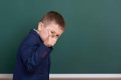 Punto del ragazzo di scuola il dito vicino al fondo in bianco della lavagna, vestito in vestito nero classico, allievo del gruppo Fotografia Stock