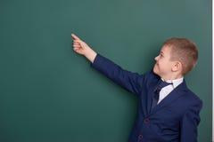 Punto del ragazzo di scuola il dito vicino al fondo in bianco della lavagna, vestito in vestito nero classico, allievo del gruppo Immagini Stock