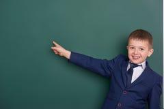 Punto del ragazzo di scuola il dito vicino al fondo in bianco della lavagna, vestito in vestito nero classico, allievo del gruppo Fotografia Stock Libera da Diritti