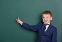 Punto del ragazzo di scuola il dito vicino al fondo in bianco della lavagna, vestito in vestito nero classico, allievo del gruppo Fotografie Stock