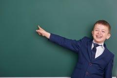 Punto del ragazzo di scuola il dito vicino al fondo in bianco della lavagna, vestito in vestito nero classico, allievo del gruppo Immagini Stock Libere da Diritti