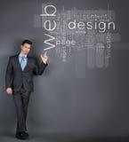 Punto dell'uomo d'affari alle parole di web design Immagine Stock Libera da Diritti