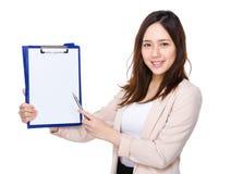Punto di penna asiatico della donna di affari alla lavagna per appunti fotografia stock libera da diritti