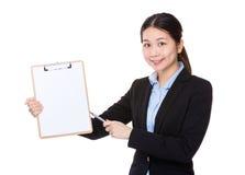 Punto di penna della donna di affari alla lavagna per appunti Immagine Stock