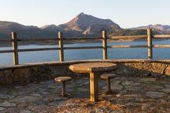 Punto di vista ad un bacino idrico con la Tabella e le sedie di pietra Fotografie Stock