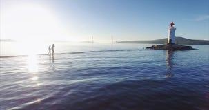 Punto di vista adorabile della famiglia che cammina lungo lo sputo, godendo del mare stupefacente e dell'alba archivi video